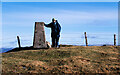 NT0529 : Trig point, fence and hill walker at summit of Culter Fell by Trevor Littlewood