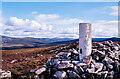 NN7795 : Trig point, rocks and low heath on Croidh-la by Trevor Littlewood