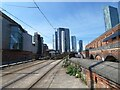 SJ8397 : Looking down the tram tracks at the towers of Manchester by Gerald England
