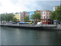O1534 : Colourful shops and bars on the banks of the Liffey by Margaret Clough