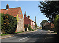 TG0536 : Holt Road (B1110) past old cottages by Evelyn Simak